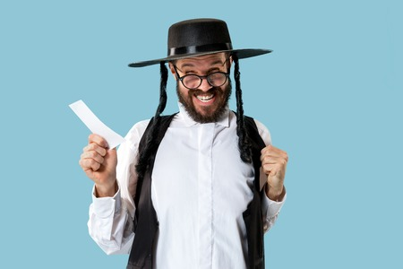 Portrait of a young orthodox Hasdim Jewish man with bet slip at studio. The holiday, celebration, judaism, bet, betting concept. Stock Photo