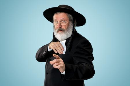 Portrait of a senior orthodox Hasdim Jewish man with bet slip at studio. The holiday, celebration, judaism, bet, betting concept.