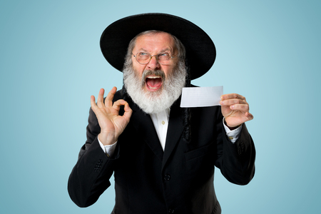 Portrait of a senior orthodox Hasdim Jewish man with bet slip at studio. The holiday, celebration, judaism, bet, betting concept.