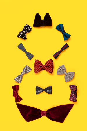 The conceptual composition from set of the bow tie about Eight march womans day holiday on a yellow background. The number 8 in decor. Top view