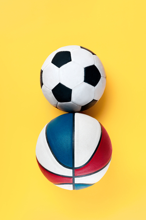The conceptual composition from soccer football and basketball balls about Eight march womans day holiday on a yellow background. The number 8 in decor. Top view. The women in sport and fitness