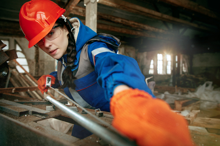 Destroying gender stereotypes. Woman wearing helmet using different male work tools. Gender equality. Girl working at flat remodeling. Building, repair and renovation. woman in the male profession Zdjęcie Seryjne