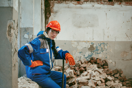 Destroying gender stereotypes. Woman wearing helmet using different male work tools. Gender equality. Girl working at flat remodeling. Building, repair and renovation. woman in the male profession 免版税图像