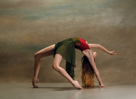 The young woman dancing in contemporary stile on gray background. Modern female dancer at studio. Elegance, grace and performance concept