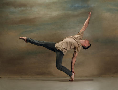 The young man dancing in contemporary stile of ballet at studio on gray background
