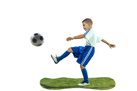 Young boy kicks the soccer ball. Isolated photo on white background. Football player in motion at studio. Fit jumping boy in action, jump, movement at game. 스톡 콘텐츠