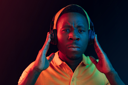 The young handsome serious sad hipster man listening music with headphones at black studio with neon lights. Disco, night club, hip hop style, positive emotions, face expression, dancing concept Stock Photo