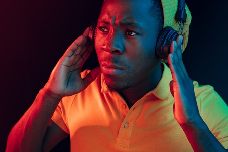 The young handsome serious sad hipster man listening music with headphones at black studio with neon lights. Disco, night club, hip hop style, positive emotions, face expression, dancing concept Banco de Imagens