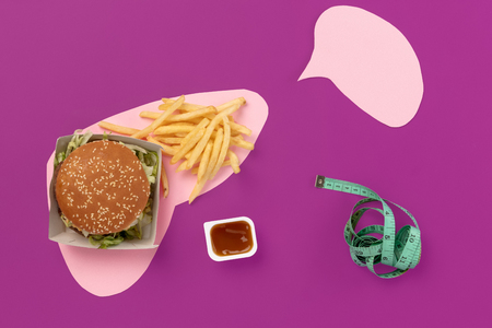 I love fast food. French fries, burger in the form of liver isolated on pink background. Unhealthy nutrition concept. Conceptual composition with copyspace Stock Photo