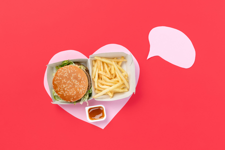 I love fast food. French fries, burger in the form of heart isolated on red background. Unhealthy nutrition concept. Conceptual composition with copyspace