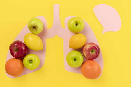 Detox food selection from fresh fruits in paper human lungs on yellow background. Healthy food nutrition. Conceptual composition with copyspace