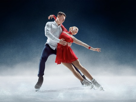 Patinadores artísticos profesionales de hombre y mujer que realizan espectáculo o competición en la arena de hielo