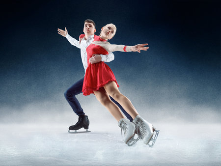 Professional man and woman figure skaters performing show or competition on ice arena Standard-Bild - 117218714
