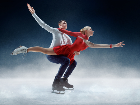 Professional man and woman figure skaters performing show or competition on ice arena