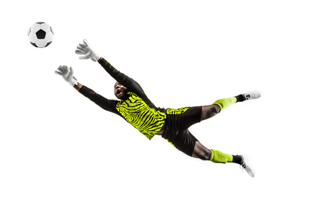 Male soccer player goalkeeper catching ball in jump. Silhouette of fit man with ball isolated on white studio background Фото со стока