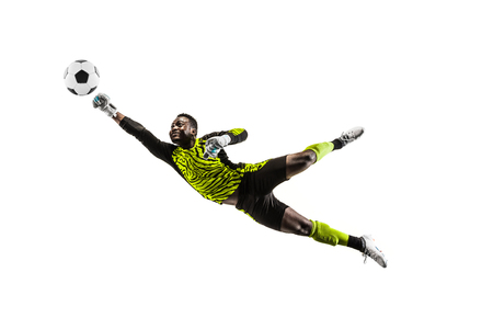 Male soccer player goalkeeper catching ball in jump. Silhouette of fit man with ball isolated on white studio background Stock Photo