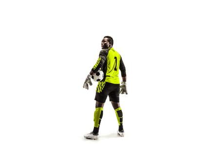 Un portiere maschio africano del calciatore che sta e che tiene palla Sagoma isolata su sfondo bianco studio Archivio Fotografico