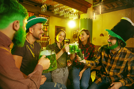 Saint Patricks Day Party. Happy friends are celebrating and drinking green beer. Young men and women wearing green hats. Pub Interior. Zdjęcie Seryjne