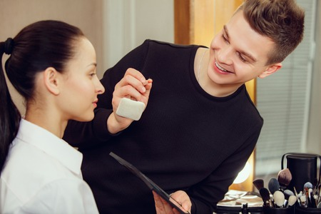 Professional makeup artist working with beautiful young woman. The man in female proffesion. gender equality concept Stock Photo