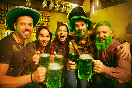 Saint Patricks Day Party. Happy friends is celebrating and drinking green beer. Young men and women wearing a green hats. Pub Interior.