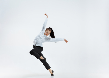 Happy businesswoman dancing and smiling in motion isolated on white studio background. Flexibility and grace in business. Human emotions concept. Office, success, professional, happiness, expression concepts