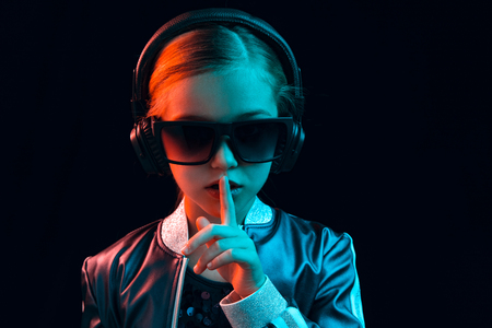 Neon portrait of young girl with headphones enjoying music and calling for silence. Lifestyle of young people, human emotions, childhood, happiness concept. Imagens