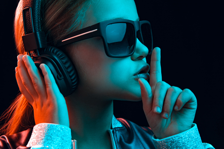Neon portrait of young girl with headphones enjoying music and calling for silence. Lifestyle of young people, human emotions, childhood, happiness concept. Stockfoto