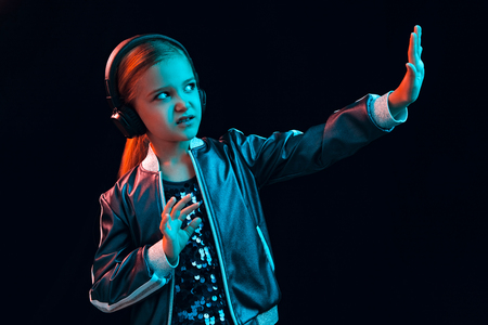 Neon portrait of young girl with headphones regecting something. Lifestyle of young people, human emotions, childhood, happiness concept.