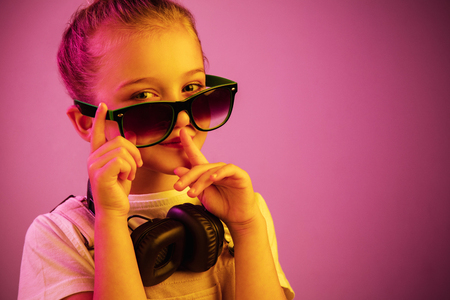 Neon portrait of young girl with headphones enjoying music and calling for silence. Lifestyle of young people, human emotions, childhood, happiness concept. 스톡 콘텐츠