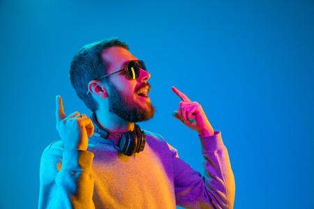 Enjoying his favorite music. Happy young stylish man in hat and sunglasses with headphones listening and smiling while standing against blue neon background Banco de Imagens