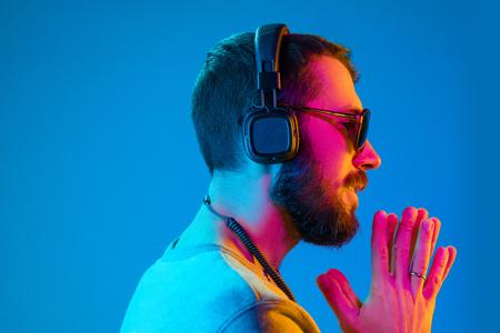 Er genießt seine Lieblingsmusik. Fröhlicher junger, stilvoller Mann mit Sonnenbrille mit Kopfhörern, der zuhört und lächelt, während er vor blauem Neonhintergrund steht