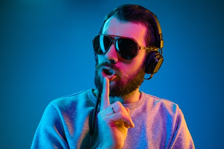 Enjoying his favorite music. Happy young stylish man in sunglasses with headphones listening sound and calling for silence while standing against blue neon background