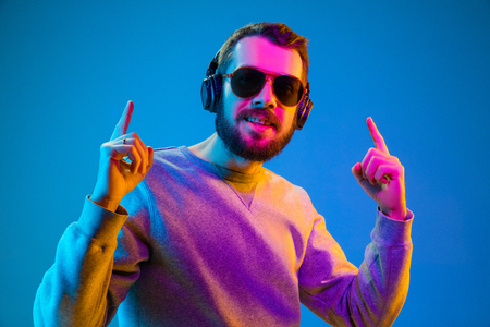 Enjoying his favorite music. Happy young stylish man in hat and sunglasses with headphones listening and smiling while standing against blue neon background Stock fotó