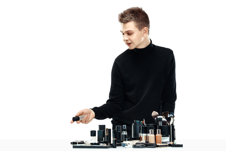 Professional makeup artist with tools isolated on white studio background. The man in female proffesion. gender equality concept Stock Photo