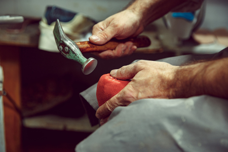 Enjoying process of craft shoes creation. Workplace of shoe designer. Hands of shoemaker dealing with cobbler tool, close up Stock Photo