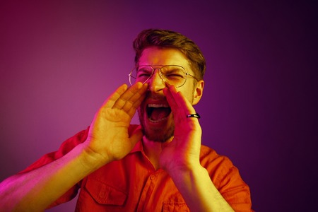 Do not miss. Young casual man shouting. Shout. Crying emotional man screaming on pink studio background. male half-length portrait. Human emotions, facial expression concept. Trendy neon colors. Synth wave style Stock Photo