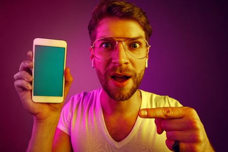 Indoor portrait of attractive young man isolated on pink neon background, holding blank smartphone, smiling at camera, showing screen, feeling happy and surprised. Human emotions, facial expression co 写真素材