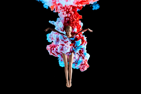 Modern art collage. Concept ballerina with colorful smoke. Abstract formed by color dissolving in water on black background Banco de Imagens