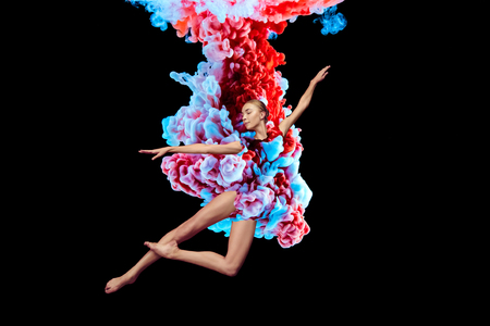 Modern art collage. Concept ballerina with colorful smoke. Abstract formed by color dissolving in water on black background Imagens