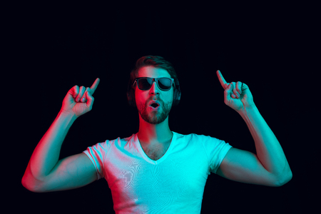 Enjoying his favorite music. Happy young stylish man in sunglasses with headphones listening sound and smiling while standing against blue neon background