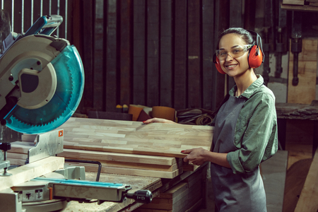 Smiling craftswoman grinding timbers with special machine. Beautiful woman wearing safety glasses. Concept of joiners shop and woodworking. Gender equality. Male profession