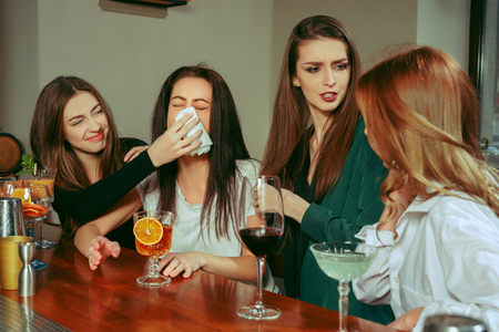 Stress. Female friends having a drinks at bar. They are sitting at a wooden table with cocktails. They are wearing casual clothes. Friends comforting and soothing a crying girl Banco de Imagens