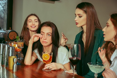 Stress. Female friends having a drinks at bar. They are sitting at a wooden table with cocktails. They are wearing casual clothes. Friends comforting and soothing a crying girl Stockfoto