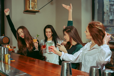 Female friends having a drinks at bar. They are sitting at a wooden table with cocktails. They are clinking glasses