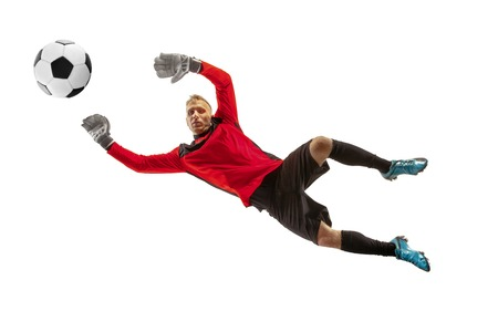 Male soccer player goalkeeper catching ball in jump. Silhouette of fit man with ball isolated on white studio background 写真素材