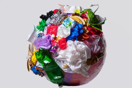 A globe of the earth with trash over white background, the concept of ecology problem and World Environment Day. Photo with message for social advertising, place for inscription Stock Photo