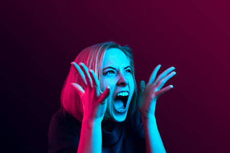 Screaming, hate, rage. Crying emotional angry woman screaming on neon studio background. Emotional, young face. Female half-length portrait. Human emotions, facial expression concept. Trendy colors 版權商用圖片 - 117525662