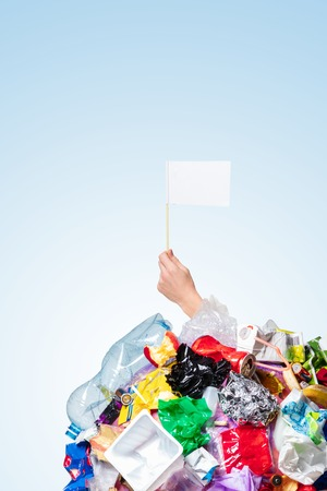 An earth globe covered with trash and male hand holding white flag over white background, the concept of ecology problem and World Environment Day. Photo with message for social advertising, place for inscription Stock Photo