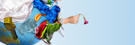 An earth globe covered with trash and male hand with a withering flower over white background, the concept of ecology problem and World Environment Day. Photo with message for social advertising, place for inscription