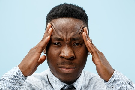 Man having headache. Isolated on blue background. The african businessman standing with pain isolated on trendy blue studio background. Male half-length portrait. Human emotions, facial expression concept.